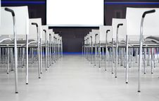 Free Low Angle Photography Of Pile Of Stainless Steel Chairs With Hanging Projector Canvas Stock Images - 109910114