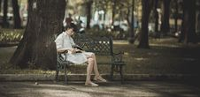 Free Woman Sitting On Metal Bench On Park While Reading Book Royalty Free Stock Photography - 109910127