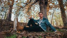 Free Man Wearing Green Jacket Sitting On Ground Near Tree Royalty Free Stock Photos - 109910338