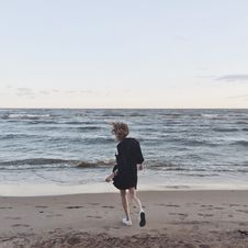 Free Woman Going Toward The Sea Under Clear Skies Stock Photos - 109910393