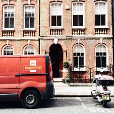 Free Red Royal Mail Parked Near Brown Brick Building Stock Photo - 109910510