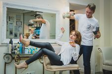 Free Woman Sitting On The Salon Chair While Holding Vodka Glass And Man At Her Back White Spraying Her Hair Royalty Free Stock Photography - 109910907
