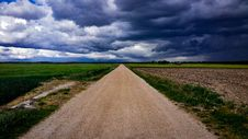 Free Dirt Road Surrounded With Green Field Under Cloudy Sky Stock Image - 109910941