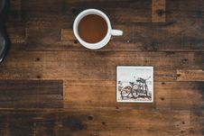 Free White Ceramic Mug With Coffee Beside Photo Of Two Mountain Bikes Royalty Free Stock Images - 109911119
