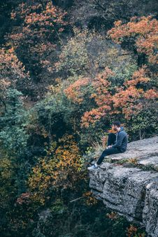 Free Photography Of Man Wearing Black Hoodie With Black Pants Sitting On Stone Cliff Above Green And Red Leaved Forest Royalty Free Stock Photography - 109911357