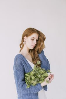 Free Woman In Blue Cardigan Holding Green Flowers Stock Image - 109911451