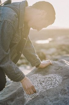 Free Man Sketching Heart On A Gray Rock Stock Photos - 109911563