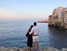 Free Man In White Dress Shirt Standing Beside The Woman In Black And Red Dress While Watching The Blue Calm Water Near Brown Concrete B Stock Photos - 109911693