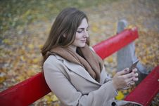 Free Woman In Beige Coat Holding Smartphone Sitting On Bench Stock Photos - 109911733