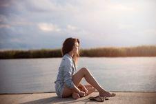 Free Woman In Blue Denim Jacket Sitting Near Body Of Water Stock Image - 109911831