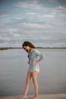 Free Woman Wearing Gray Denim Tie-front Long-sleeved Shirt And Short Shorts Walking On Isle Near Body Of Water Royalty Free Stock Photography - 109911857