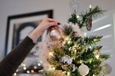 Free Person Holding Beige Bauble Near Christmas Tree Stock Photography - 109911862