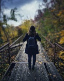 Free Selective Focus Photography Of Woman Wearing Black Overcoat Standing On Wooden Bridge Stock Photography - 109911932