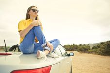Free Woman Wears Yellow Shirt And Blue Denim Jeans Sits On Silver Car Royalty Free Stock Photos - 109912108