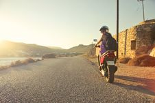 Free Woman Riding Motor Scooter Travelling On Asphalt Road During Sunrise Stock Photography - 109912142
