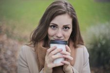 Free Woman In Brown Top And Scarf Holding A White And Black Travel Cup Outside Stock Images - 109912184