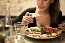 Free Woman Holds Sliced Pizza Seats By Table With Glass Stock Photo - 109912230