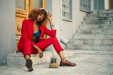 Free Woman Wearing Red Blazer And Pants Sitting On Marble Ground Stock Images - 109912494