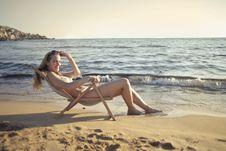 Free Woman Sitting On Sun Chair Beside Seashore At Daylight Photography Stock Photos - 109912513