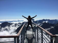Free Person Standing On Hand Rails With Arms Wide Open Facing The Mountains And Clouds Stock Photos - 109912733