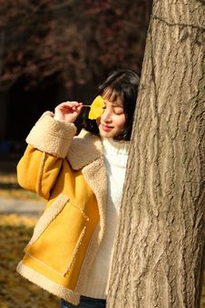 Free Woman Wearing Yellow Jacket Holding Yellow Leaf Stock Photos - 109913043