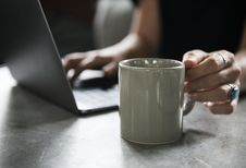 Free Person In Black Top Holding White Ceramic Mug And Using Laptop Computer Royalty Free Stock Image - 109913076