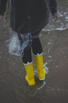 Free Person Wearing Clear Plastic Raincoat And Pair Of Yellow Rainboots Stock Images - 109913134