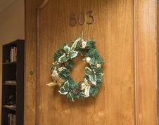 Free Christmas Wreath Hanging On Brown Wooden Door Of Room 803 Royalty Free Stock Photography - 109913157