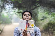 Free Man In Grey Shirt Holding Opened Book Looking Upward Royalty Free Stock Photos - 109913238