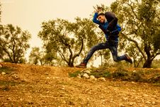 Free Man Wearing Blue And Black Shirt Jumping While Holding Brown Jacket Taken During Golden Hour Royalty Free Stock Images - 109913569
