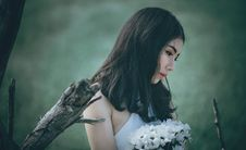 Free Woman In White Top Holding Bouquet Of White Petaled Flowers While Looking Down Stock Photo - 109913690