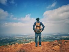 Free Man In Blue Dress Shirt And Blue Jeans And Orange Backpack Standing On Mountain Cliff Looking At Town Under Blue Sky And White Clo Royalty Free Stock Photography - 109913947