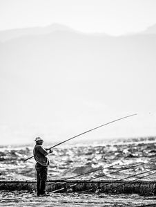 Free Man Standing Near Seashore Holding Fishing Rod On Grayscale Photography Stock Images - 109914174