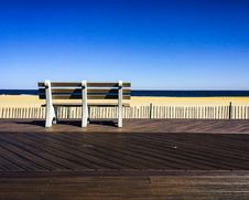 Free Brown-and-white Wooden Bench Facing Body Of Water Under Clear Blue Sky Stock Photos - 109914193