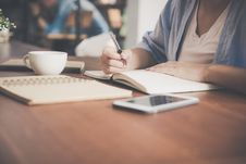 Free Woman Writing On A Notebook Beside Teacup And Tablet Computer Stock Images - 109914204
