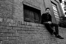 Free Grayscale Photography Of Man Sitting On Brick Fence Royalty Free Stock Photo - 109914205
