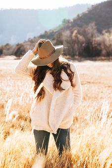 Free Smiling Woman In White Winter Jacket Wearing Brown Cowboy Hat Surrounded Of Brown Grass Field Stock Image - 109914211
