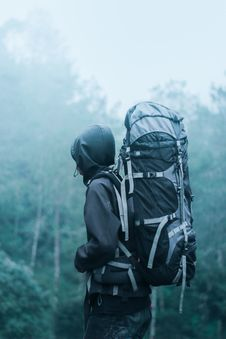 Free Man Wearing Black Hoodie Carries Black And Gray Backpacker Near Trees During Foggy Weather Royalty Free Stock Image - 109914236