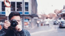 Free Man Holding A Camera On Busy Street Stock Photography - 109914352