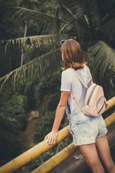 Free Woman Wearing Dungaree Shorts Stands Near A Yellow Metal Rail Overlook A River Belo With Coconut Trees At Daytime Royalty Free Stock Images - 109914379