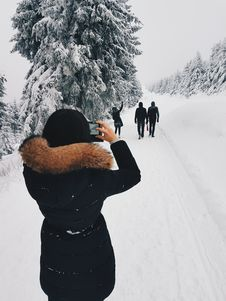 Free Woman In Black Coat Taking A Picture Of Three Person In Front Of Her While Walking Through Snow Field Royalty Free Stock Images - 109914569