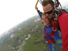 Free Couple Wears Red And Blue Long-sleeved Overalls And Body Harness With Parachute On Mid-air Stock Photo - 109914630