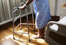 Free Person In Hospital Gown Using Walking Frame Beside Hospital Bed Royalty Free Stock Images - 109914859