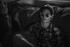 Free Grayscale Photo Of Man Wearing Snapback Cap And Plaid Dress Shirt Sitting On Couch Stock Images - 109914864