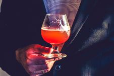 Free Person Holds Clear Glass Snifter With Red Beverage Royalty Free Stock Images - 109914889