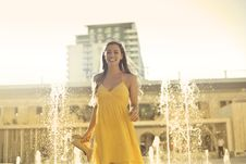 Free Woman Wears Yellow Spaghetti Strap Dress Stands Near Water Fountain Royalty Free Stock Image - 109915186
