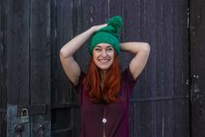 Free Woman In Green Bobble Cap And Purple T-shirt Posing Near Black Wooden Fence Stock Image - 109915321