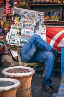Free Man Sitting On Plastic Armchair Reading Newspaper Royalty Free Stock Photo - 109915505