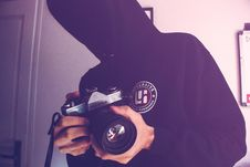 Free Man Holding Black And Gray Dslr Camera Inside White Wall Paint Room Stock Photos - 109915803