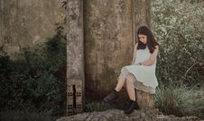 Free Woman Sitting On Slab Near Brown Wall Royalty Free Stock Image - 109915966